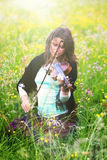 Violinist auf einer Wiese voll von Blumen, junges Mädchen, das Musikinstrument spielt Lizenzfreie Stockfotografie