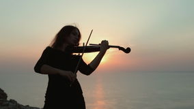 Violinist on the background of an incredibly. Violinist in dress playing on the background of an incredibly beautiful sunset on the sea stock video footage