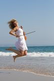Violinist beach jump Royalty Free Stock Image
