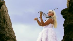 Violinist In A Beautiful White Dress. Beautiful violinist clad in a beautiful white dress playing the violin. Against the backdrop of a beautiful sky stock video footage