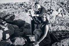 Violinist and the girl sitting on stones Stock Photography