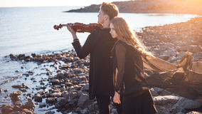 Violinist and girl,  young man plays on the Stock Image