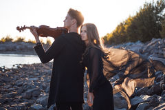 Violinist and girl,  young man plays on the Royalty Free Stock Image