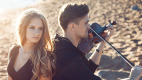Violinist and girl,  young man plays on the Stock Photo