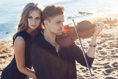Violinist and girl,  young man plays on the Stock Images