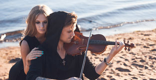 Violinist and his Muse,   young man plays on the Stock Photography