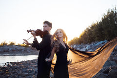 Violinist and his Muse,   young man plays on the Royalty Free Stock Image