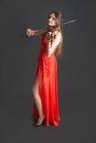 Violinist i röd klänning royaltyfria bilder