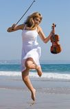 violinist jump on beach Stock Photo