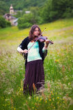Violinist on a meadow full of flowers Royalty Free Stock Photo