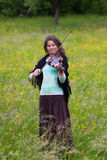 Violinist on a meadow full of flowers, Young girl playing music instrument. Stock Photo