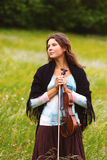 Violinist on a meadow full of flowers, Young girl playing music instrument. Vintage picture Stock Photo