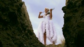 Violinist In The Mountains Playing An Instrument. Beautiful violinist clad in a beautiful white dress playing the violin. Against the backdrop of a beautiful sky stock footage