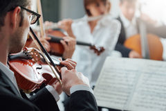 Violinist performing with classical orchestra Royalty Free Stock Photos