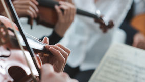 Violinist performing on stage with orchestra Stock Photography