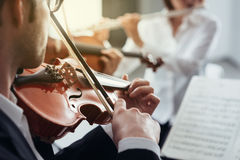 Violinist performing on stage with orchestra Royalty Free Stock Images