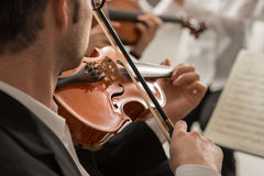 Violinist performing on stage with orchestra stock image