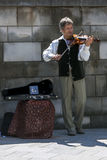 A violinist performs in Krakow in Poland. A violinist performs on the sidewalk in Krakow in Poland Stock Photos