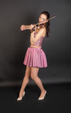 Violinist in pink corset. And skirt on black background royalty free stock image