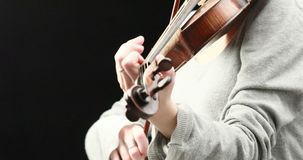 Violinist playing - closeup of her hands. Classical musician playing baroque violin on a black background - hands closeup live action concept stock video