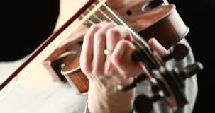 Violinist playing - closeup of her hands. Classical musician playing baroque violin on a black background - hands closeup live action concept stock video footage