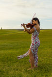 Violinist playing on the grass Royalty Free Stock Photography
