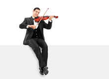 Violinist playing seated on a blank panel. Isolated on white background Royalty Free Stock Image