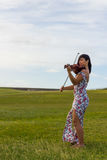 Violinist playing to the wind. Girl playing violin in a park at sunset Stock Images