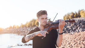 Violinist playing a violin,  young man plays on Royalty Free Stock Image