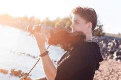 Violinist playing a violin,  young man plays on Royalty Free Stock Images