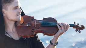 Violinist playing a violin,  young man plays on. Violinist playing a violin, on the background of the sea Stock Photography