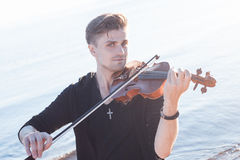 Violinist playing a violin,  young man plays on Royalty Free Stock Photos