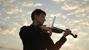 Violinist plays against the sunset. Violin on sunset. stock footage
