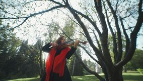 Violinist plays in autumn forest and inspired by nature. stock video footage
