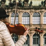 Violinist plays a beautiful wooden violin on the street of the o stock photo