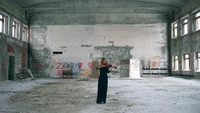 A violinist plays fiddle while performing alone in abandoned building. 4K stock video footage