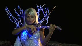 Violinist Plays In The Magical Dress. Beautiful violinist dressed as a magical fairy plays the violin. Dress with shining lights stock video footage