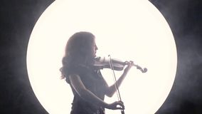 Silhouette of a girl-musician. The violinist plays the violin in smoke against a white circle. The violinist plays the violin in smoke against a white circle stock video footage