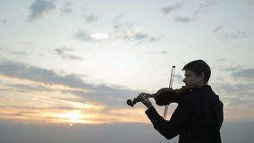 Violinist puts musical instrument on his shoulder and begins to play. stock video