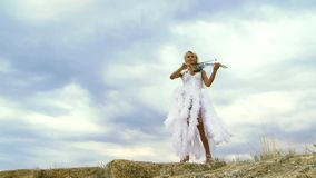 Violinist Skyline Plays The Violin. Beautiful violinist clad in a beautiful white dress playing the violin. Against the backdrop of a beautiful sky stock video