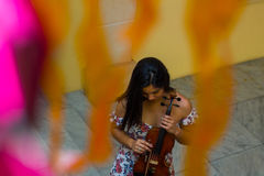 Violinist unaware. Violinist checking her instrument before playing Stock Image