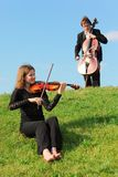 Violinist and violoncellist play against sky Stock Images