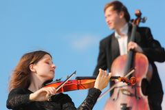 Violinist and violoncellist play against sky Royalty Free Stock Images