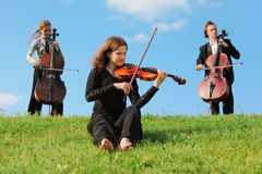 Violinist and violoncellists play against sky Stock Photos