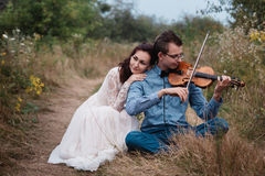 Violinist and woman in white dress , young man plays on the violin the background nature Stock Image