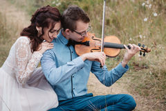 Violinist and woman in white dress , young man plays on the violin the background nature Stock Photos