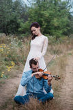 Violinist and woman in white dress , young man plays on the violin the background nature Royalty Free Stock Image