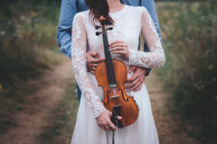 Violinist and woman in white dress , young man plays on the violin the background nature. Violinist and women in white dress , young men plays on the violin the Stock Photos