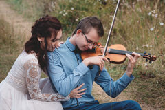 Violinist and woman in white dress , young man plays on the violin the background nature Stock Images