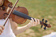 Violinist woman. Young woman playing a violin. Outside stock image